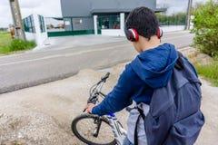 Giovane studente con lo zaino e la bicicletta, ascoltanti la musica fotografie stock