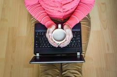 Giovane studente con una tazza di caffè facendo uso del computer portatile Immagine Stock Libera da Diritti