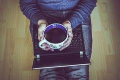 Giovane studente con una tazza di tè facendo uso di un computer portatile e di seduta sul Th Immagine Stock