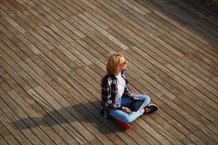 Giovane studente dei capelli biondi che si siede sul pilastro di legno che distoglie lo sguardo, sole del chiarore Fotografie Stock