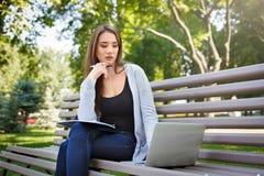 Giovane studente della femmina l'IT su un banco, Fare compito nel parco con il computer portatile ed il manuale Fotografie Stock