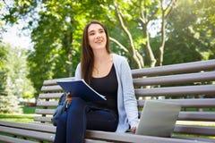 Giovane studente della femmina l'IT su un banco, Fare compito nel parco con il computer portatile ed il manuale Immagini Stock Libere da Diritti
