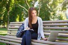 Giovane studente della femmina l'IT su un banco, Fare compito nel parco con il computer portatile ed il manuale Fotografie Stock Libere da Diritti