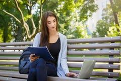 Giovane studente della femmina l'IT su un banco, Fare compito nel parco con il computer portatile ed il manuale Fotografia Stock