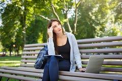 Giovane studente della femmina l'IT su un banco, Fare compito nel parco con il computer portatile ed il manuale Immagine Stock