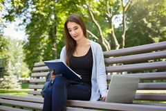 Giovane studente della femmina l'IT su un banco, Fare compito nel parco con il computer portatile ed il manuale Fotografia Stock Libera da Diritti