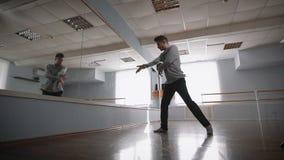 Giovane studente della scuola di dancing che fila e che balla vicino allo specchio Il bello uomo di dancing sta mostrando la pass archivi video