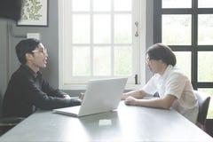 Giovane studente delle coppie che discute le cose e che lavora ad un progetto mentre sedendosi alla scuola Immagine Stock