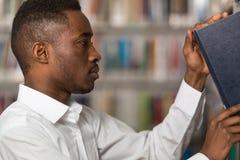 Giovane studente di college bello in una libreria Immagine Stock Libera da Diritti