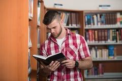 Giovane studente di college bello in una libreria Fotografia Stock