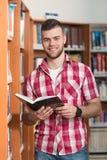 Giovane studente di college bello in una libreria Immagini Stock Libere da Diritti
