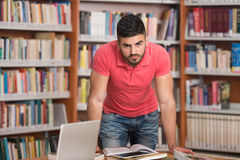 Giovane studente di college bello in una libreria Fotografia Stock Libera da Diritti