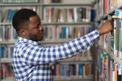 Giovane studente di college bello in una libreria Fotografie Stock Libere da Diritti