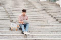 Giovane studente di college che per mezzo del computer portatile che si siede sulle scale Fotografia Stock Libera da Diritti