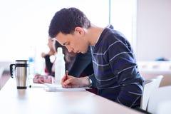 Giovane, studente di college maschio bello che si siede in un'aula in pieno Fotografia Stock