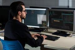 Giovane studente di informatica che si sviluppa con il suo computer su un sistema di Linux sopra il doppio sistema dello schermo fotografia stock libera da diritti