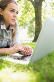Giovane studente di pensiero che si trova sull'erba facendo uso del suo computer portatile Immagini Stock