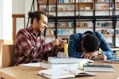 Giovane studente divertente dell'uomo che si siede nella biblioteca vicino all'amico stanco Fotografie Stock Libere da Diritti