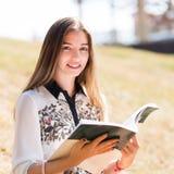 Giovane studente europeo con il libro di esercizi a all'aperto Fotografia Stock