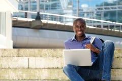 Giovane studente felice che si siede sui punti con il computer portatile Fotografia Stock Libera da Diritti