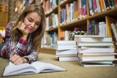 Giovane studente felice che si trova sul libro di lettura del pavimento delle biblioteche Fotografia Stock Libera da Diritti