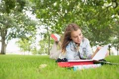 Giovane studente felice che studia sull'erba Fotografia Stock Libera da Diritti