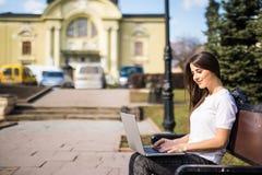Giovane studente felice con il computer portatile che si siede sul banco Fotografie Stock Libere da Diritti