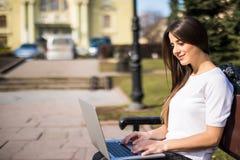 Giovane studente felice con il computer portatile che si siede sul banco Immagini Stock