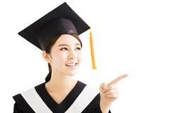 Giovane studente femminile asiatico di graduazione che indica e che guarda Fotografia Stock