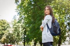 Giovane studente femminile dell'asiatico l'IT, con i libri e lo zaino Restando nel parco e sorridere Immagine Stock