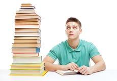 Giovane studente frustrato che si siede allo scrittorio con l'alto sta dei libri Fotografia Stock Libera da Diritti