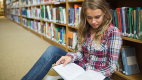 Giovane studente grazioso che si siede sul libro di lettura del pavimento delle biblioteche Immagine Stock