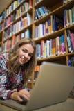 Giovane studente grazioso che si trova sul pavimento delle biblioteche facendo uso del computer portatile Immagini Stock