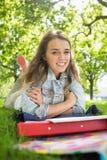 Giovane studente grazioso che si trova sull'erba che sorride alla macchina fotografica Fotografie Stock