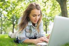 Giovane studente grazioso che si trova sull'erba facendo uso del computer portatile Immagine Stock