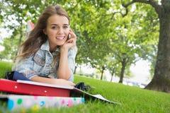 Giovane studente grazioso che si trova sull'erba sul telefono Fotografie Stock Libere da Diritti