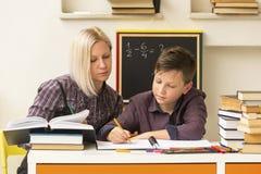Giovane studente impegnato con l'insegnante aiuto Fotografie Stock Libere da Diritti