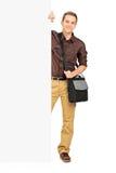Giovane studente maschio che sta dietro un pannello fotografie stock libere da diritti