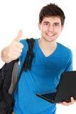 Giovane studente maschio con il computer portatile che mostra pollice su Fotografia Stock