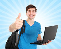Giovane studente maschio con il computer portatile che mostra pollice su Immagini Stock Libere da Diritti