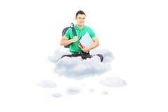 Giovane studente maschio con la borsa e taccuini che si siedono su una nuvola Fotografie Stock