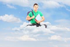 Giovane studente maschio con la borsa e taccuini che si siedono su una nuvola Immagini Stock