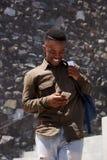 Giovane studente maschio nero felice che ride con il telefono cellulare Fotografia Stock