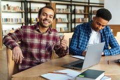 Giovane studente maschio sorridente che mostra i pollici su Immagine Stock Libera da Diritti