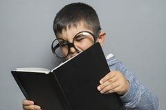 Giovane studente moro sveglio che legge un libro divertente, lettura e Fotografie Stock