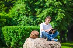 Giovane studente in parco fuori con il taccuino e Fotografia Stock Libera da Diritti