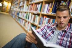 Giovane studente serio che si siede sul libro di lettura del pavimento delle biblioteche Fotografie Stock Libere da Diritti