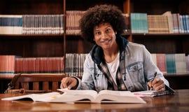 Giovane studente sicuro che studia nella biblioteca Fotografia Stock Libera da Diritti