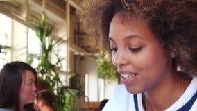 Giovane studente solo della donna di colore di Portret enorme dal suo compito in caffè Agli studenti allegri del gruppo del fondo stock footage