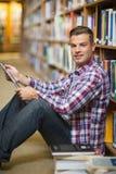 Giovane studente sorridente che si siede sul pavimento delle biblioteche facendo uso della compressa Fotografie Stock